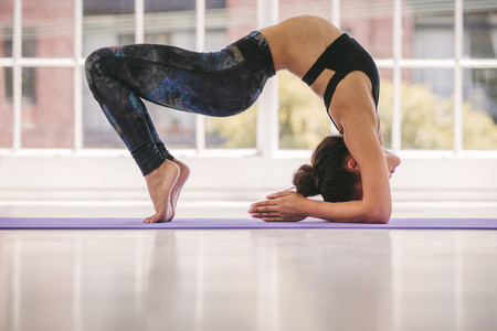 Young female doing bridge yoga pose in gym class