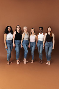Six diverse women holding hands  Group of multi ethnic females of different ages looking at camera