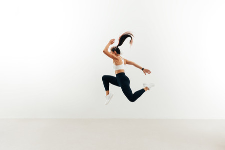 Side view of woman with muscular body jumping against white wall