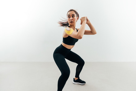 Woman with kinesiology tape on her shoulder exercising indoors  Young female doing sit ups