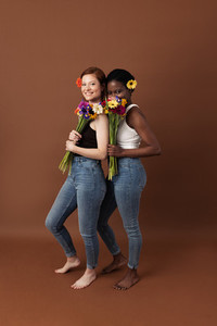 Two women with different skin color posing against a brown background  Cheerful females with flowers standing together looking at camera