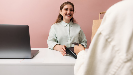 Happy clothing store owner looks at the buyer while he pays with credit card