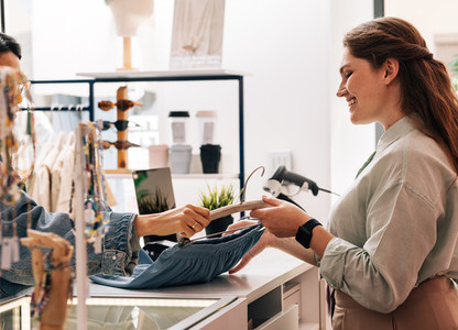 Side view of saleswoman helping buyer with clothes at fashion store