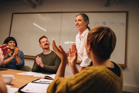 Business team appreciating effort of coworker in meeting