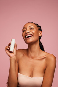 Woman holding a skincare product and smiling