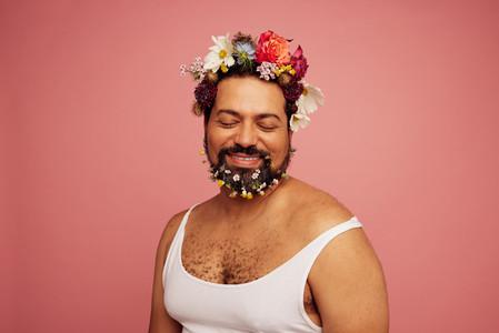 Genderqueer wearing flowers on head and beard