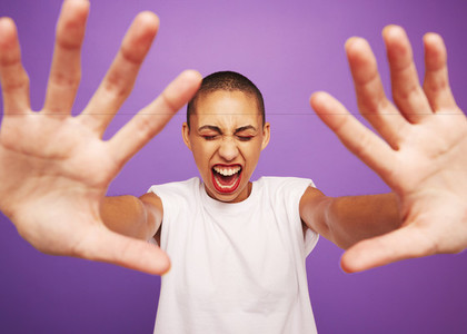 Excited woman screaming on purple background