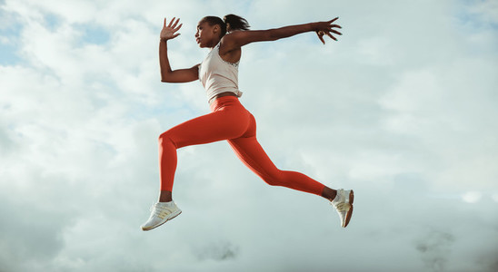Athletic woman running and jumping outdoors