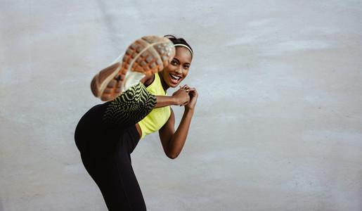 African sportswoman doing kick boxing exercise