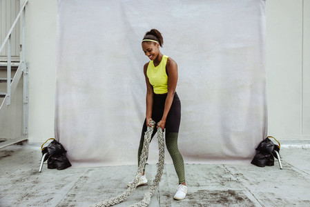 African woman doing battle rope workout