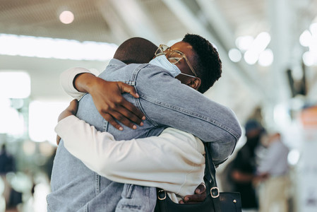 African couple reuniting at airport arrivals