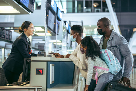 Ground staff assisting family at checkin counter during pandemic