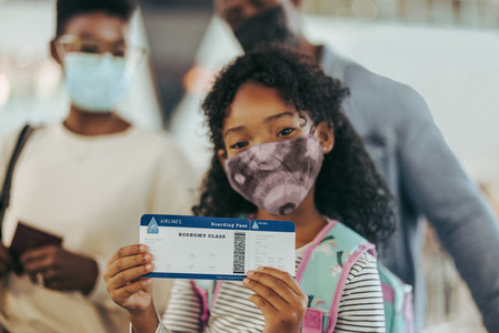 Girl showing boarding pass with family at airport