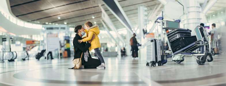 Happy mother and son meeting at airport after pandemic