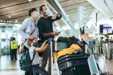Family with luggage at airport during pandemic
