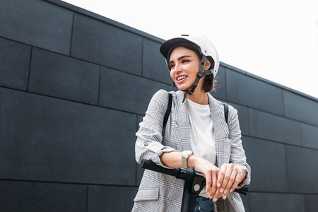 Cheerful businesswoman in cycling helmet leaning on a handlebar of e scooter while standing at a wall