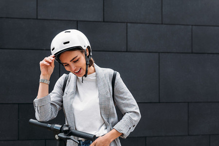 Laughing businesswoman holding a white helmet and looking down at black wall