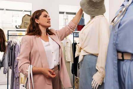 Woman buyer takes off a hat from a mannequin in a small boutique