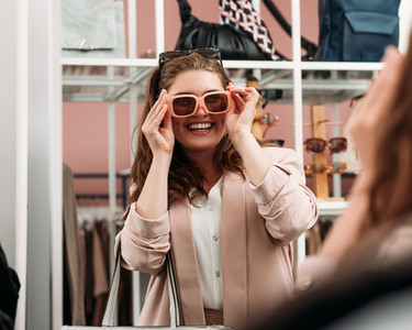 Laughing woman try on sunglasses in front of a mirror in a fashion store