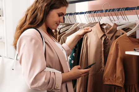 Side view of elegant woman looking at a smartphone while holding hanger with dress