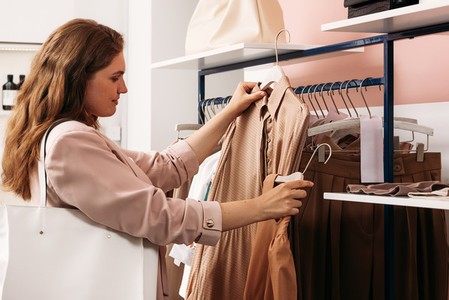 Stylish female buyer holding hangers with dresses in shop
