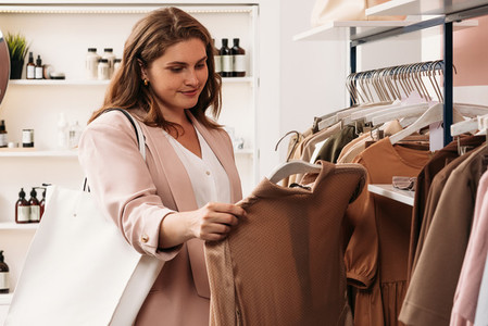 Woman holding a hanger with a dress in a small store