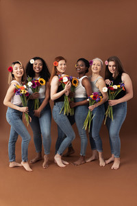 Full body shot of six women of different ages standing together with bouquets of flowers  Smiling women in casuals with flowers in hair