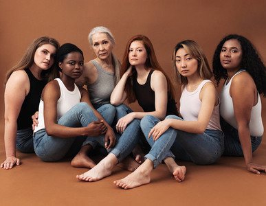 Diverse women in casuals sitting on brown background  Multi ethnic group of females looking at camera in studio