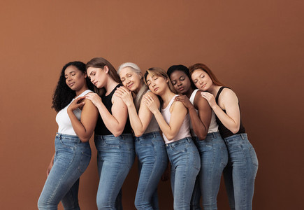 Diverse women in casuals embracing each other while standing with closed eyes over brown background