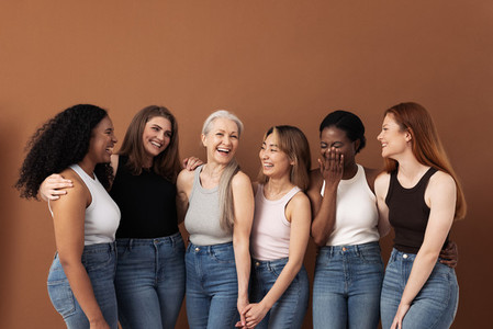 Stylish women of different ages having fun while wearing jeans and undershirts over brown background