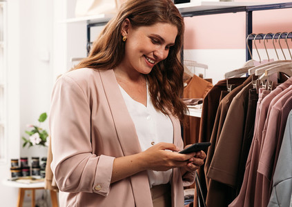 Cheerful buyer standing with mobile phone in boutique and typing