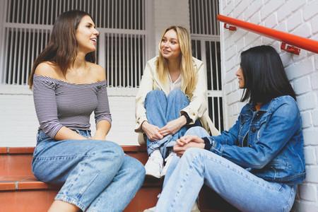 Multi ethnic group of three friends sitting on street steps talking