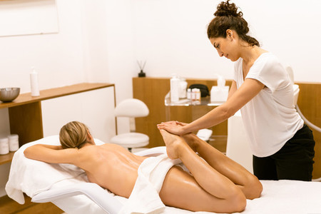 Middle aged woman having a leg massage in a beauty salon