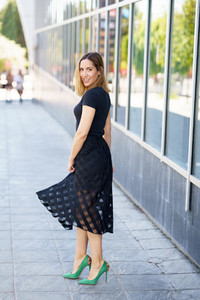 Attractive woman wearing skirt and green high heels outdoors