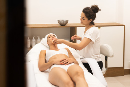 Aesthetics cleaning the skin to the face of a middle aged woman in modern wellness center