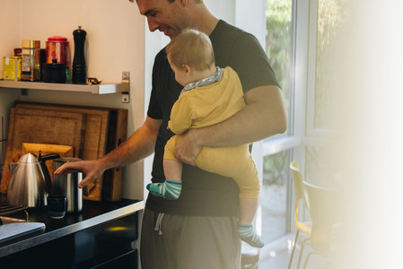 Man making coffee with baby