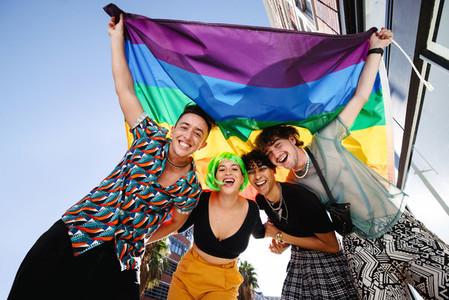 Smiling queer people celebrating pride together