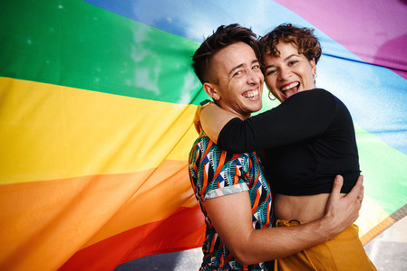 Smiling queer couple standing against a rainbow flag