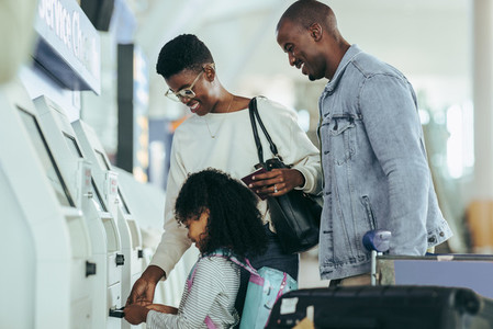 Family check in using self service machine at airport