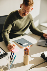 Businessman making notes working at desk