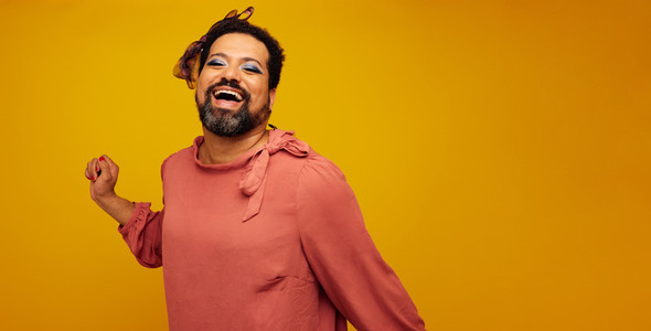 Genderqueer smiling on yellow background