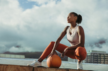 Fitness woman relaxing with ball on rooftop