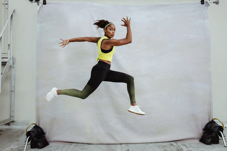 African sportswoman doing running and lunge exercise