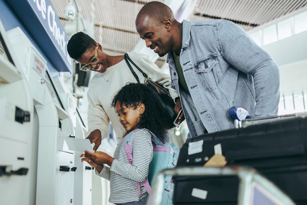 Tourist family doing self service check in for flight