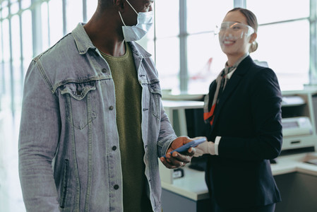 Man in face mask passing by airport check in counter