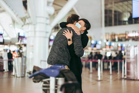 Woman embracing man at airport after long separation