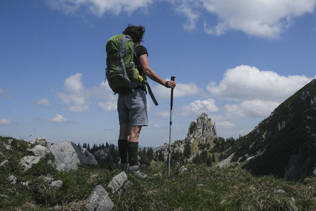 Woman with backpack hiking in sunny mountains Germany