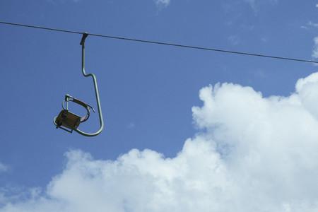 Empty ski lift chair against sunny blue sky