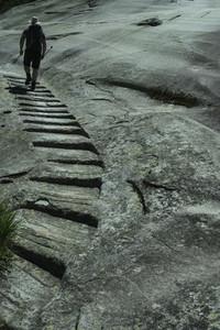 Man hiking along rock pathway Haehlen Platte Grimselweg Switzerland