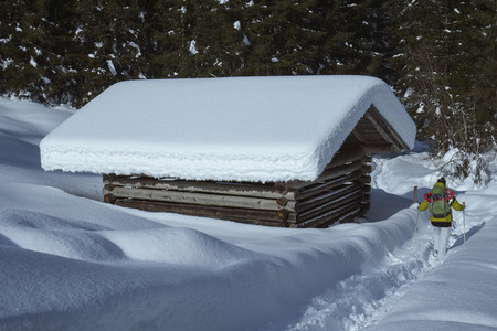 Woman snowshoeing in deep snow along hut Germany